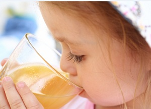 child drinking juice from a juicer